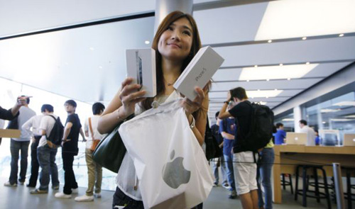 A customer shows her new iPhone 5 at the Apple store in Hong Kong on Sept. 21, 2012. /AP