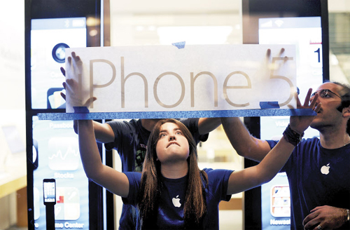 Apple employees hang an iPhone 5 sign at one of the companys retail locations shortly before sales began in San Francisco, California on Friday. /Reuters-Newsis