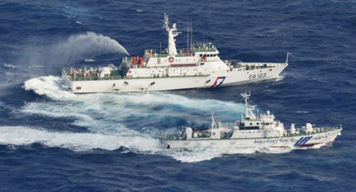 A Japanese Coast Guard patrol ship (center) sprays water at a fishing boat from Taiwan, as Taiwans Coast Guard vessel (top) sprays water near the disputed islands in the East China Sea on Sept. 25, 2012. /Reuters