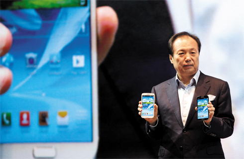 Shin Jong-kyun, the head of Samsungs mobile communications business, shows the Galaxy Note 2 smartphone at a launch in Seoul on Wednesday. 