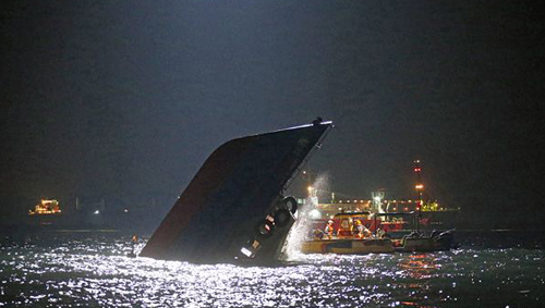 Rescuers check on a half submerged boat after it collided Monday night near Lamma Island, off the southwestern coast of Hong Kong Island on Oct. 2, 2012. /AP