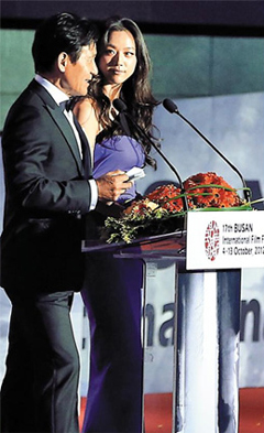 Korean actor Ahn Sung-ki (left) and Chinese actress Tang Wei host the opening ceremony of the 17th Busan International Film Festival at the outdoor theater of the Busan Cinema Center on Thursday. /Yonhap
