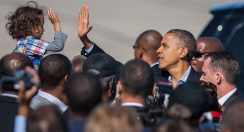 President Barack Obama high-fives with a child as he arrives at the Newport News/Williamsburg International Airport in Newport News, Virginia on Oct. 13, 2012. /AP