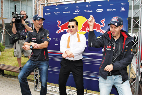 Red Bull's Sebastian Vettel and his teammate Mark Webber learn from singer Psy his signature horse riding dance at the Formula One Korean Grand Prix in Yeongam, South Jeolla Province on Sunday. /Yonhap