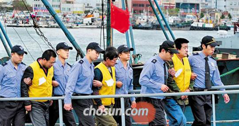 Coast Guard members guard Chinese fishermen in Mokpo, South Jeolla Province on Wednesday.