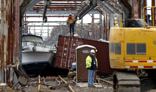 Workers try to clear boats and debris from the New Jersey Transit Morgan draw bridge in South Amboy, New Jersey after Mondays storm surge from Sandy pushed boats and cargo containers onto the train tracks on Oct. 31, 2012. /AP