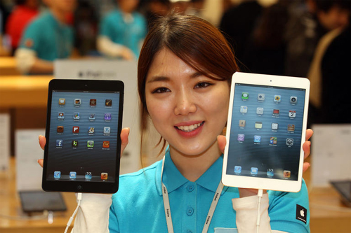 A staffer shows new iPad Minis at an Apple store in Myeong-dong, Seoul on Friday, when the smaller version of the iPad tablet went on sale.