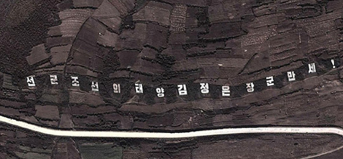 This Google Earth satellite photo taken in Oct. 6 shows a giant slogan carved into a hillside near a lake in Ryanggang Province, North Korea.