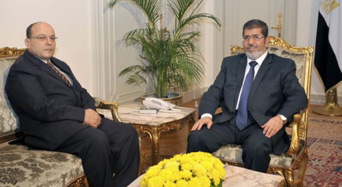 In this photo released by the Egyptian Presidency, President Mohamed Morsi (right) poses for a photograph with his new Prosecutor General, Talaat Abdullah in Cairo, Egypt on Nov. 22, 2012. /AP