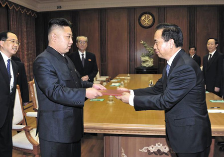 North Korean leader Kim Jong-un (left) is given a letter from new Chinese leader Xi Jinping by Li Jianguo in Pyongyang on Friday. /[North] Korean Central News Agency