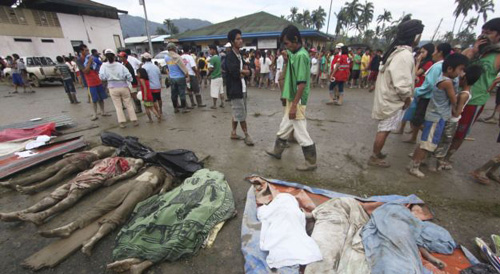 Residents pass by bodies recovered from flashflood in New Bataan, Compostela Valley province, southern Philippines on Dec. 5, 2012. /AP
