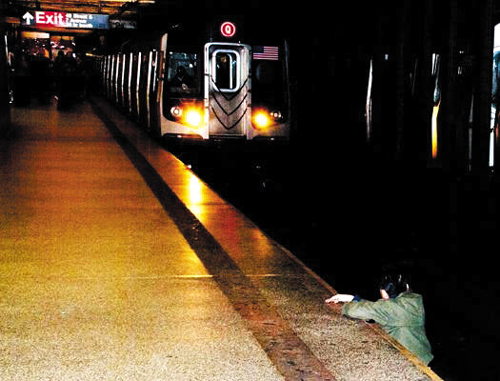 A Korean-American man tries to climb to safety after being pushed on the subway tracks in New York in this picture featured on cover of the New York Post on Tuesday.