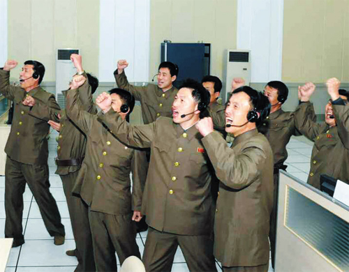 Scientists and technicians celebrate after the launch of a rocket in Pyongyang on Wednesday. /Yonhap