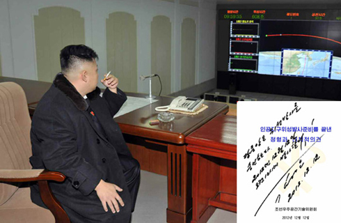 North Korean leader Kim Jong-un smokes a cigarette while waiting for the launch of a rocket last Wednesday on the outskirts of Pyongyang. A copy of the letter (right corner) apparently written by Kim shows his approval of the rocket launch. /Rodong Sinmun-Yonhap