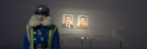 Huge portraits of North Korean founder Kim Il-sung and his son Kim Jong-il are seen behind traffic police in Kim Il-sung Square in Pyongyang on Monday, the first anniversary of Kim Jong-ils death. /AP-Newsis