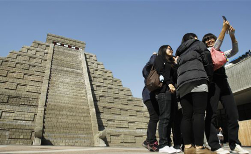 Students take pictures of themselves in front of a mock pyramid during the countdown to when many believe the Mayan people predicted the end of the world on Dec. 21, 2012 in Taichung, southern Taiwan. /AP