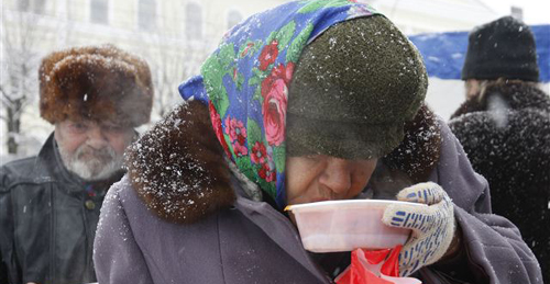 A homeless woman has a charity meal distributed by volunteers in Russias southern city of Stavropol on Dec. 25, 2012. /Reuters