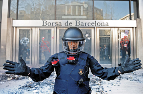 A riot policeman blocks demonstrators from barging in the Barcelona Stock Exchange building in Spain in March.