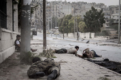A rebel army soldier crawls to rescue a citizen shot by government forces near Aleppo in Syria on Oct. 20.