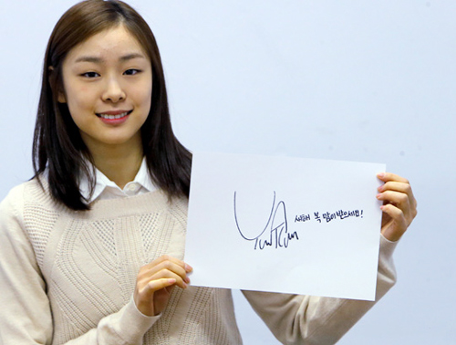 Kim Yu-na holds up a New Years message on Thursday.