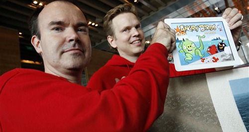 Peter Vesterbacka, Mighty Eagle, Chief Marketing Officer, left, and Henri Holm, Senior Vice President Of Rovio Asia, right, show the latest version of Angry Birds after the opening ceremony of the Shanghai office of Rovio, maker of popular computer game. /AP