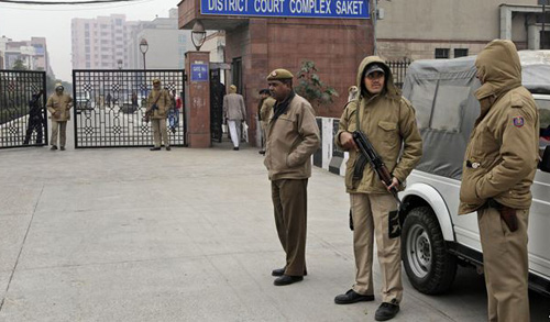 Indian police officers stand outside the district court where five men accused in a gang rape were brought to appear in New Delhi on Jan. 7, 2013. /AP