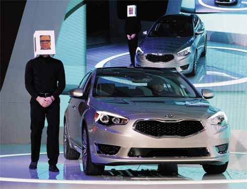 A model, with an image of Kia President and Chief Design Officer Peter Schreyer atop his head, presents the Kia Cadenza at the North American International Auto Show in Detroit, Michigan on Tuesday. /Reuters-Newsis