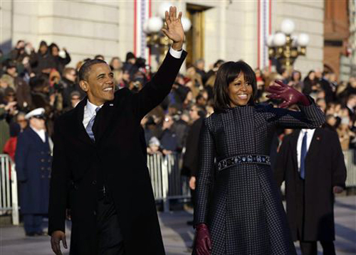 President Barack Obama and first lady Michelle Obama waves as they walk down Pennsylvania Avenue near the White House during the inauguration parade on Jan. 21, 2013. /AP