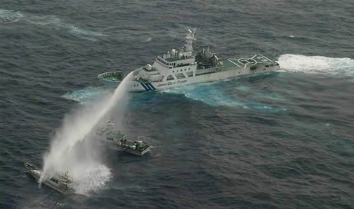 In this photo released by Japan Coast Guard 11th Regional Headquarters, a Japanese Coast Guard patrol boat uses water cannon to warn a Taiwanese leisure boat (left) and a Taiwanese Coast Guard boat off Uotsuri in Japanese and Diaoyu Dao in Chinese on Jan. 24, 2013. /AP