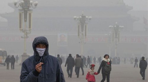 A man wears a mask on Tiananmen Square in thick haze in Beijing on Jan. 29, 2013. Extremely high pollution levels shrouded eastern China for the second time in about two weeks. /AP