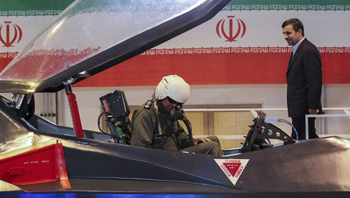 Iranian President Mahmoud Ahmadinejad listens to an unidentified pilot during a ceremony to unveil Irans newest fighter jet, Qaher-313, or Dominant-313, which officials claim can evade radar in Tehran on Feb. 2, 2013. /AP