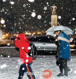 People walk in the snow in Gwanghwamun, Seoul on Sunday.
