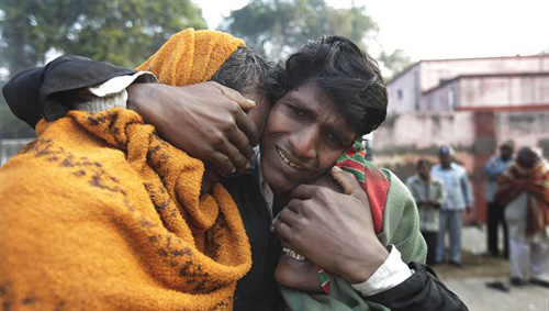An Indian man whose two relatives died in a stampede at a railway station cries and comforts other relative as they arrive to take the bodies from a morgue, in Allahabad, India on Feb. 11, 2013. /AP