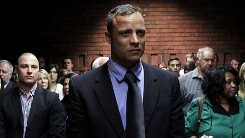 Oscar Pistorius awaits the start of court proceedings while his brother Carl (left) looks on, in the Pretoria Magistrates court on Feb. 19, 2013. /Reuters