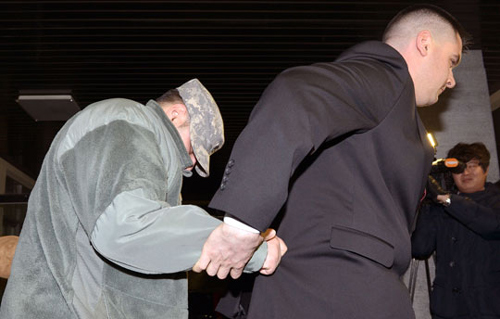 A U.S. soldier (left) leaves Yongsan Police Station in Seoul after being questioned on Monday over a high-speed car chase. /Newsis