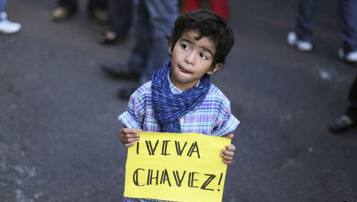 A boy holds a sign that reads 