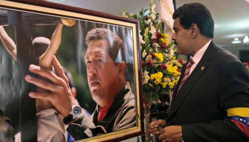 Venezuelas acting President Nicolas Maduro stands in front of a portrait of Venezuelas late President Hugo Chavez after a symbolic swearing in ceremony on March 8, 2013. /AP