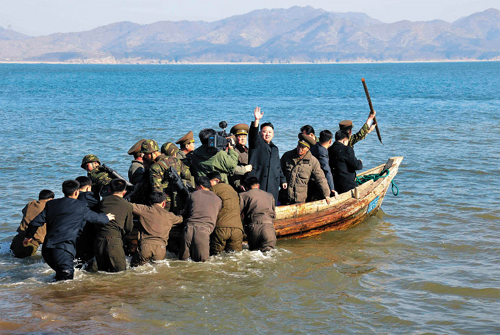 North Korean leader Kim Jong-un waves at officers after inspecting a military unit on Wolnae island near the western sea border with South Korea, in this photo released on Tuesday by the [North] Korean Central News Agency.