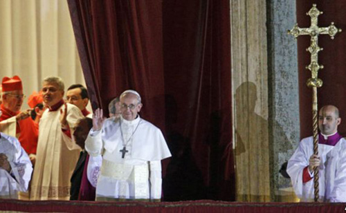 Pope Francis waves to the crowd from the central balcony of St. Peters Basilica at the Vatican on March 13, 2013. /AP