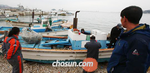 Fishermen check their boats at anchor on Yeonpyeong Island on Wednesday.