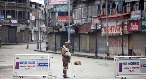 An Indian policeman stands guard at a temporary checkpoint during a curfew in Srinagar, India on March 14, 2013. /AP