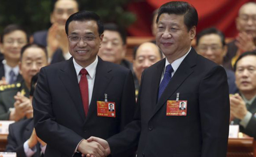 Chinas President Xi Jinping shakes hands with Chinas newly elected Premier Li Keqiang (left) as other delegates clap during the fifth plenary meeting of the first session of the 12th National Peoples Congress in Beijing on March 15, 2013. /Reuters