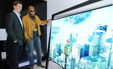 NFL quarterback Eli Manning (left) and hip-hop artist Flo Rida look at a Samsung 85-inch UHD TV in New York on Wednesday. /Courtesy of Samsung Electronics