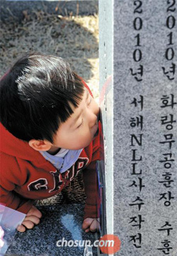 A child kisses a tombstone at the tomb of his uncle, who died when North Korea sank the Navy corvette Cheonan, at the National Cemetery in Daejeon on Saturday.