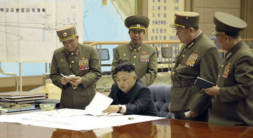 North Koreas official KCNA news agency on March 29, 2013 shows North Korean leader Kim Jong-un discussing the strike plan with North Korean officers during an urgent operation meeting at the Supreme Command in an undisclosed location. /AFP