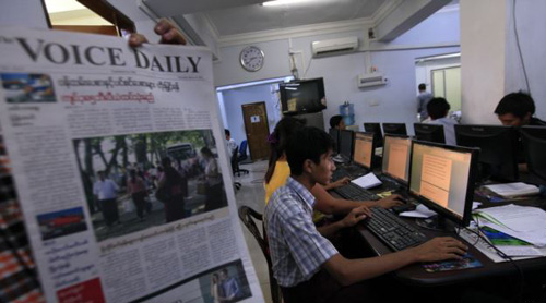 Journalist holds up a sample copy of The Voice Daily newspaper at a news room in Rangoon, Burma on March 31, 2013. /Reuters
