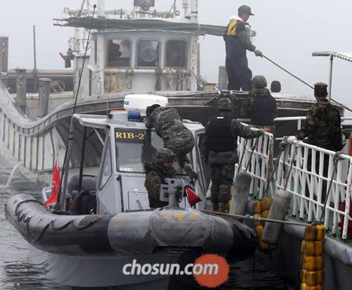 Coast guards check a fishing boat at a port on Yeonpyeong Island on Thursday morning.