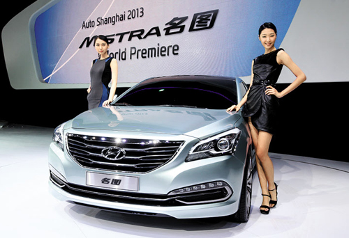 Models pose next to Hyundai's mid-size sedan, Mistra at the Shanghai Auto Show in Shanghai, China on Saturday.