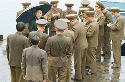 North Korean leader Kim Jong-un (with umbrella) inspects a fishery station in this photo released by North Koreas KCNA news agency on Tuesday. /Rodong Sinmum
