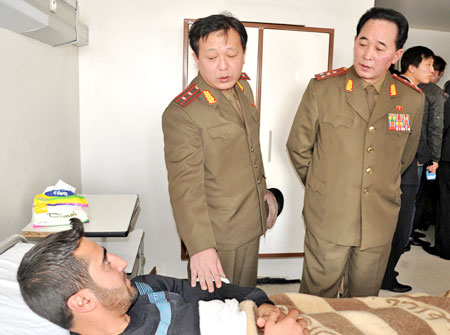 This handout picture from the Syrian Arab News Agency shows two military attaches from the North Korean Embassy in Syria during a visit to the Tishreen Military Hospital in Damascus on March 6, 2012.